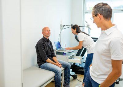 Dr Kuehnel und Ordinationsassistentin Elisabeth bei der Untersuchung mit einem Patienten im Behandlungsraum
